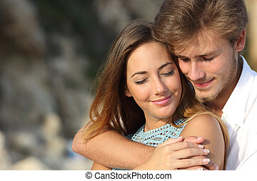 Couple in love hugging and feeling the romance with closed eyes outdoors