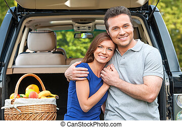 Couple in love hugging each other with car on background.