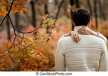 Couple in love hugging in beautiful autumn day in park.