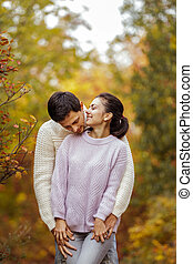 Couple in love hugging on beautiful autumn day in park.