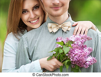 couple in love in park smiling holding a bouquet of lilac flowers in their hands. Valentine's Day