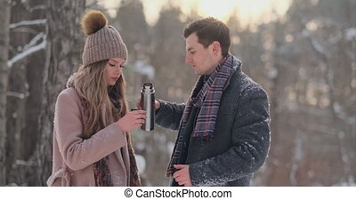 Couple in love in the winter forest to drink tea from a...
