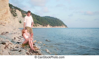 Couple in love is sitting on a rock near the sea in togetherness at sunset.
