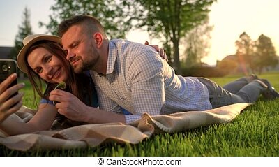 Couple in love lies on a plaid in the park and making self...