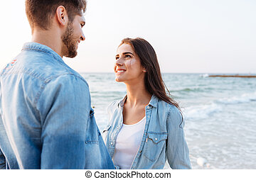Couple in love looking at each other on the beach