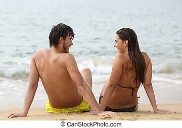 Couple in love looking each other on the beach