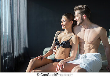 Couple in love looking towards the sun from a luxurious hotel room while beain half naked