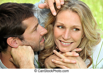 Couple in love lying in the grass