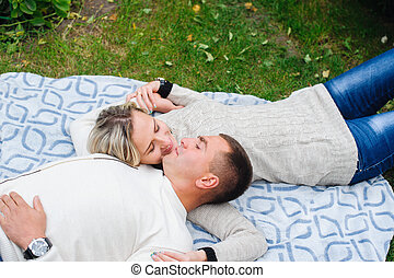 couple in love lying on the plaid in the park