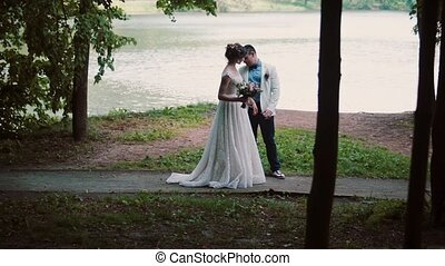 Couple in love on a river bank on their wedding day. Happy bride turns and shows her beautiful dress to her groom