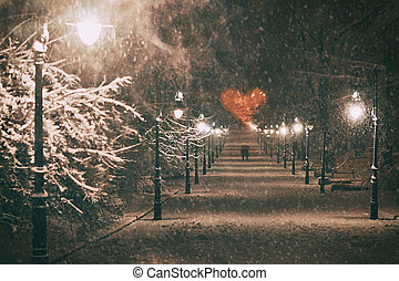 Couple in love on a romantic date walks through the snowy night winter park alley with beautiful lanterns covered with snow to the heart formed by tree branches on St Valentine day
