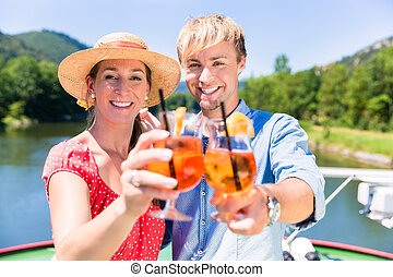 Couple in love on river cruise drinking coctails in summer