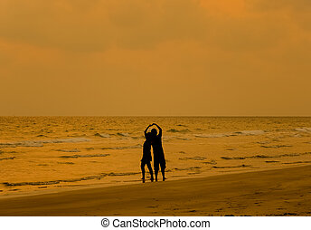 Couple in love on the beach over a beautiful sunset