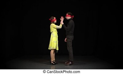 The guy and the girl are looking for each other blindfolded on a black background in the studio. The concept of relationships, loneliness, love, separation, meeting. Slow motion