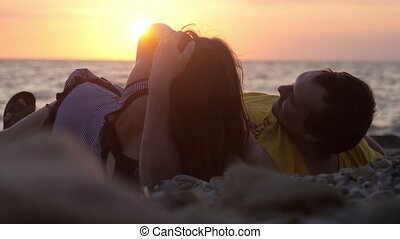 Couple in love romantically lay under the sun kissing together looking amazing sunset by the sea in slow motion.