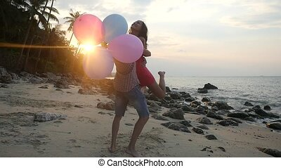Couple in love run to each other. Man holding multicolored balloons hugging her girl spin around. Couple have enjoying vacation on tropical beach with beautiful lens flare effects. slow motion.