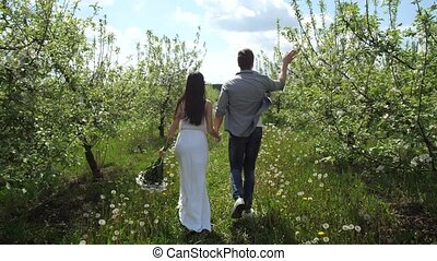 Couple in love running holding hands in orchard