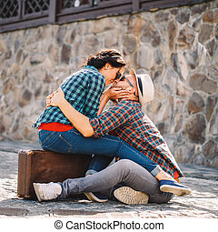 couple in love sitting on road with suitcase