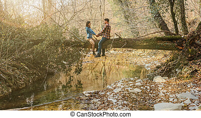 Couple in love sitting on tree trunk in forest