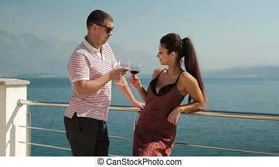 Couple in love standing on loggia and drinking wine and communicate.