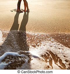 couple in love standing on the sand by the sea, sunset