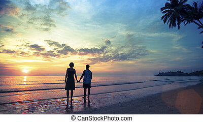 Couple in love standing on the seashore watching a wonderful sunset. Honeymoon.