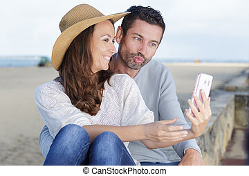 couple in love taking a selfie at the beach