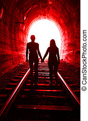 Couple in love walking together through a railway tunnel