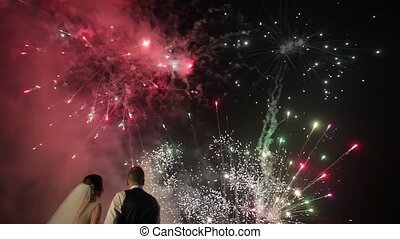 Couple in love watching fireworks. Silhouette newlyweds on fireworks background