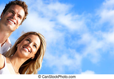 Couple in love - Young love couple smiling under blue sky