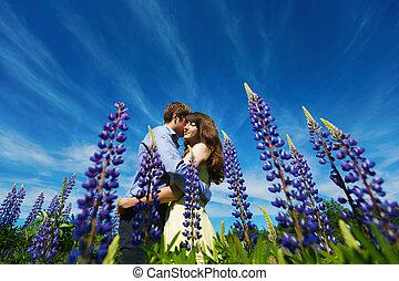 Couple in lupine flowers field