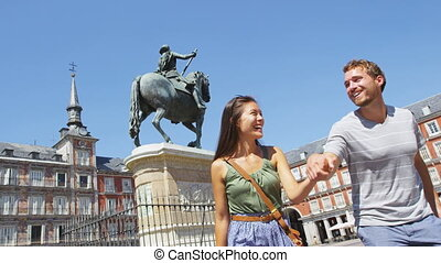 Couple in Madrid Spain on Plaza Mayor walking and running ...