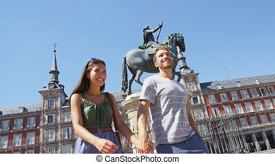 Couple in Madrid Spain on Plaza Mayor walking holding hands...