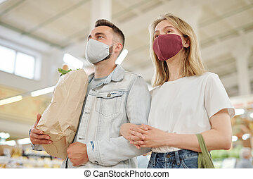 Couple in masks buying food