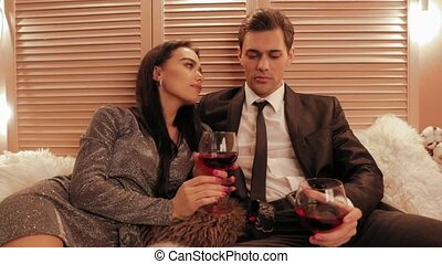 Couple in passion drink red wine and cheers for new year in...