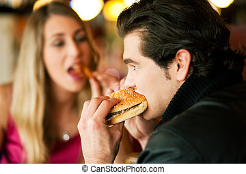 Couple in Restaurant eating fast food - Couple in a ...