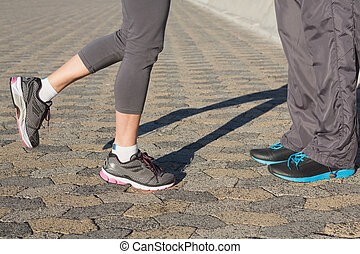 Couple in running shoes facing
