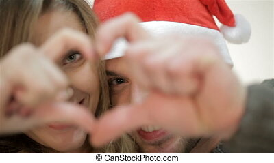 Couple in Santa hat make fingers image heart.
