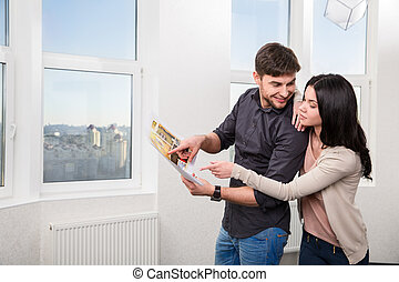 couple in searching the real estate for a purchase - young...