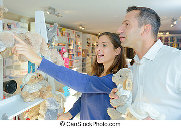 Couple in shop looking at soft toys