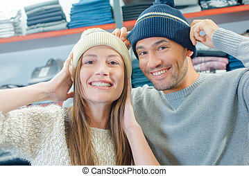 Couple in shop trying on beeny hats