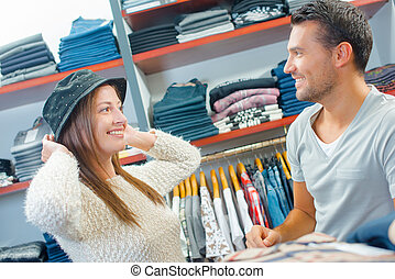 Couple in shop trying on hat