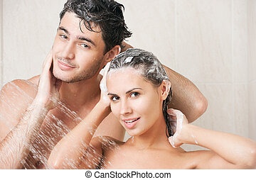 Couple in shower - Young couple washing their heads in the...