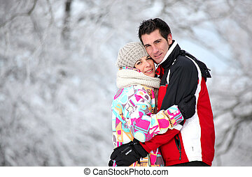 Couple in ski jackets hugging on a winter's day