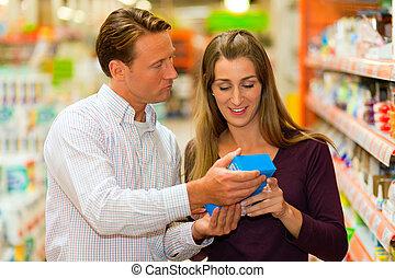 couple in supermarket choosing groceries