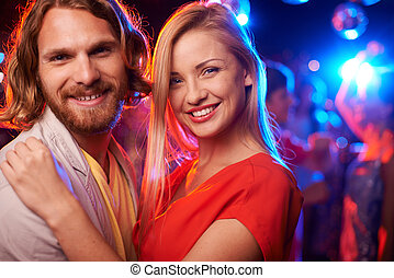 Couple in the club - Happy beautiful couple embracing at...