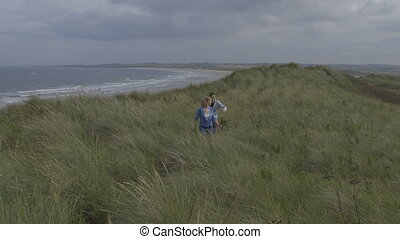 Couple in the dunes - A happy young couple laugh and smile...