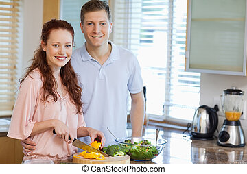 Couple in the kitchen preparing salad