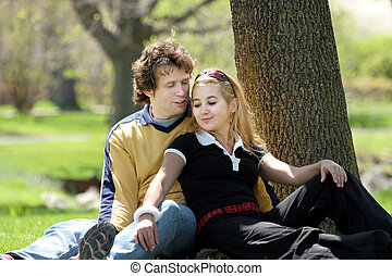 Couple in the park - Romantic couple sitting in a park.