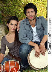 Couple in the park with bongo drums